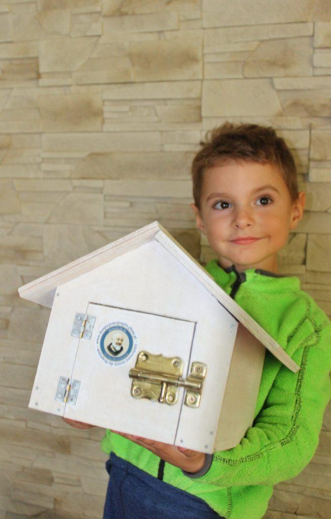 Uśmiechnięte dziecko trzymające zbudowany przez siebie i tatę drewniany domek