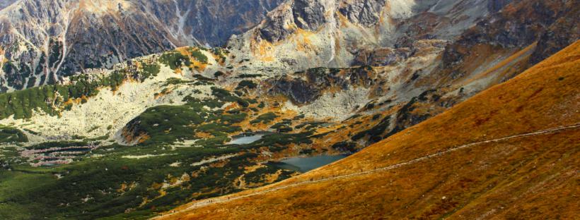 widok na stawy z Kasprowego Wierchu, jesienna sceneria, żółta trawa, oświetlone przez słońce szczyty