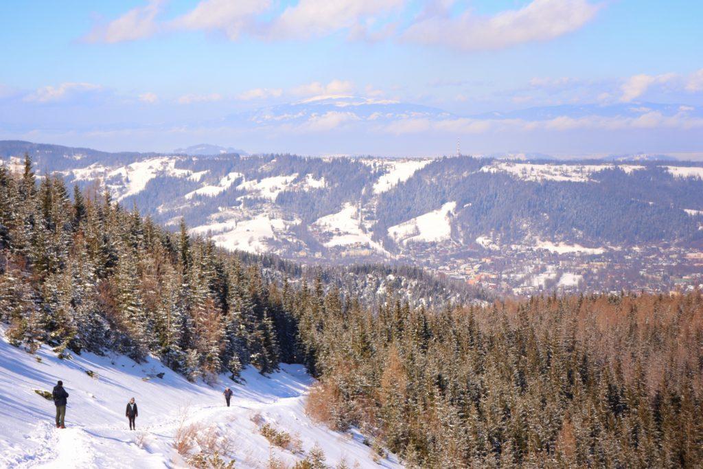 Turyści podchodzący niebieskim szlakiem w kierunku Przełęczy między Kopami, zima