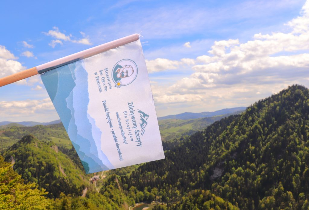 Flaga akcji Zdobywamy Szczyty dla Hospicjum, Sokolica w Pieninach, krajobraz górski, błękitne niebo z białymi obłokami