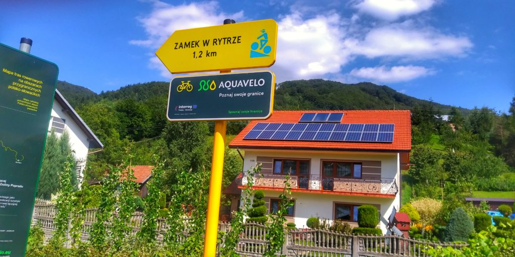 Ulica Sucha Struga, Rytro, żółta tabliczka z napisem Zamek w Rytrze 1,2 kilometra, w tle dom