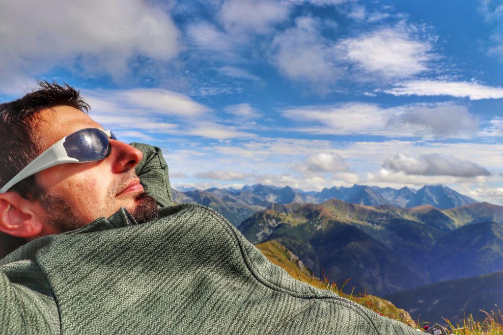 Turysta odpoczywający na szczycie dwutysięcznika - Ciemniak, w tle tatrzańskie szczyty