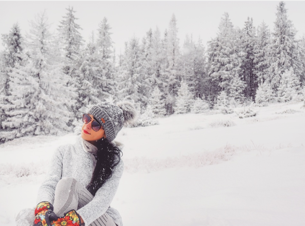 Turystka siedząca na śniegu, w tle ośnieżone drzewa, Beskid Żywiecki