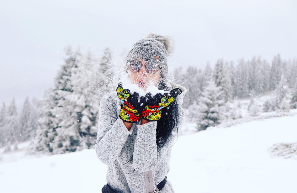 Turystka zdmuchująca z dłoni śnieg, zimowa Hala na Muńczole