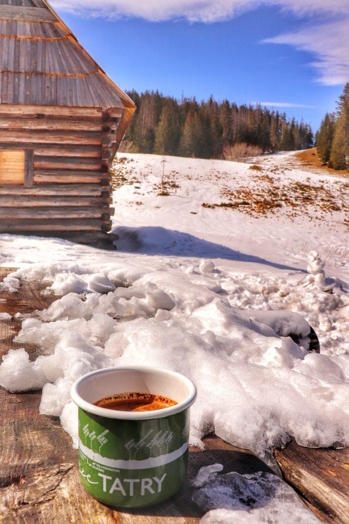 Zielony kubek z napisem TATRY, który jest wypełniony kawą stojący na drewnianym, zaśnieżonym stole na Polanie Olczyskiej